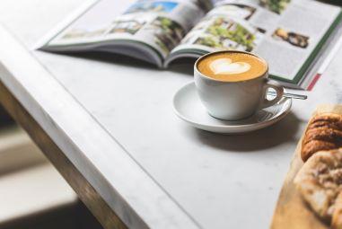 Cappuccino und Zeitschrift auf Tisch